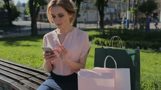 Shopping woman sitting on bench after shopping and sending sms