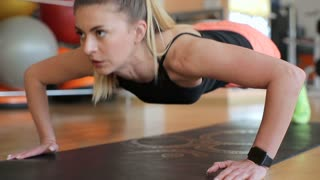 Sportswoman exercising in the gym. Muscular young woman doing pushups on exercise mat.
