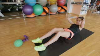 Sportswoman on exercise mat shakes press in gym. Muscular female athlete doing abs workout.