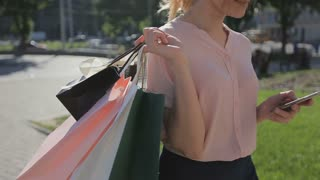 Steadicam shot of a blonde woman with colorful shopping bags using smartphone and walking in a city
