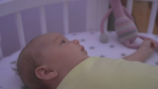 The baby lies in bed and looks at the toys