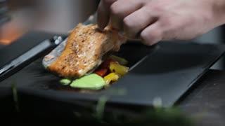 The chef decorates a fish dish