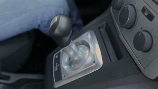 The driver shifts gears on an automatic transmission.