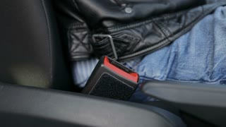 The driver wear a seat belt sitting in the car.
