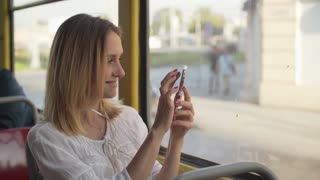 The girl makes a photo on her smartphone in a tram