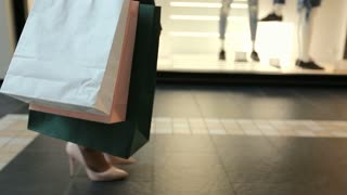 The young pretty woman walks with shopping bags in the trade center