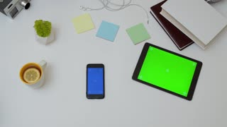 Top view on the office desk and black smartphone with blue screen and male hands taping and scrolling on it. Office stuff and tablet computer with green screen beside. Vertical. Tracking motion. Chroma key.