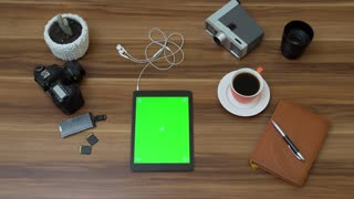 Top view on the office desk and black tablet computer with green screen. Photo camera stuff and coffee beside. Vertical. Tracking motion. Chroma key.