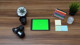 Top view on the office table with tablet computer with green screen. Photo camera stuff beside. Tracking motion. Chroma key.