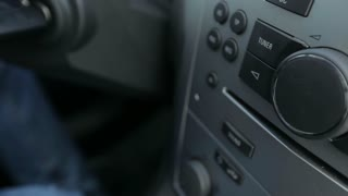 Tuning Radio Volume. Close up of hand adjusting car radio volume
