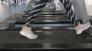 View of female legs walking and running on treadmill in gym, woman training