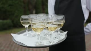Waiter holds a tray with champagne glasses
