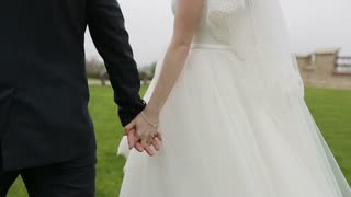 Wedding couple holding hands walking on the grass