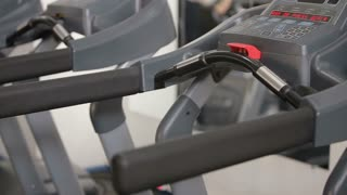 Woman adjusts the treadmill at the beginning of training, do fitness in the sport club