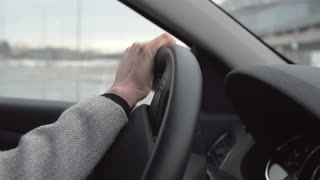 Woman drives a car in the city - detail of steering wheel and hand