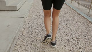 Woman feet jogging up stairs, close up. Steadicam stabilized shot. Sportswoman wearing barefoot sports shoes while training on the stairs.