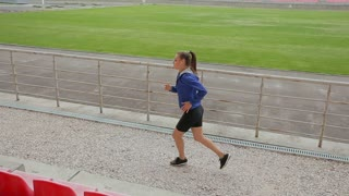 Woman feet jogging up stairs. Steadicam stabilized shot. Sportswoman wearing barefoot sports shoes while training on the stairs.