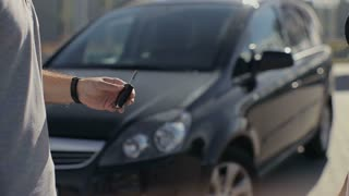 Woman getting new car keys of a black car.