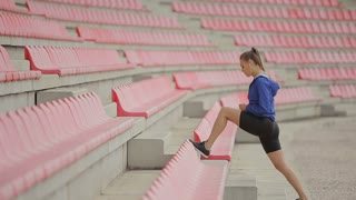 Woman jogging up stairs. Steadicam stabilized shot. Sportswoman wearing barefoot sports shoes while training on the stairs.