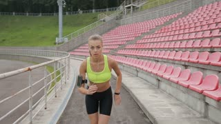 Woman running and listening to music at the sports stadium