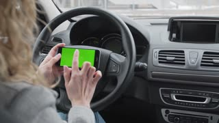 Woman sits in the modern car and works on smartphone - closeup hands. Green screen.Chroma key
