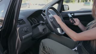 Woman sits in the modern car and works on smartphone - closeup hands.