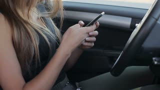 Woman sitting in her own car, contacting with someone through her smartphone phablet, technology