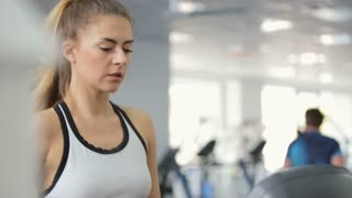 Woman starting workout on treadmill using fitness app on smartwatch.
