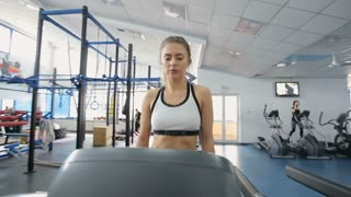 Woman starting workout on treadmill using fitness app.
