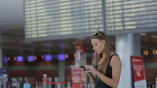 Woman using cellphone at airport
