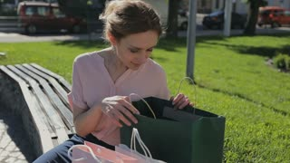 Woman with shopping bags sitting on the bench considering buying