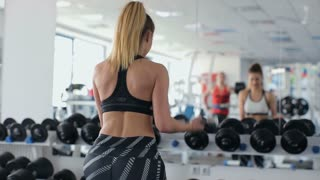 women lifting dumbbell in the fitness gym