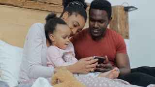 Young african american family watching cartoons on smartphone with her daughter