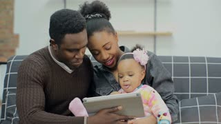 Young african american family watching cartoons on TabletPC with her daughter