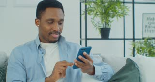Young African American man holding smartphone watching social media stories video using mobile app sitting on couch.