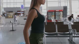 Young and beautiful woman is walking airport hall
