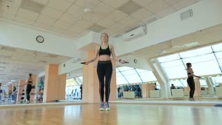 Young athletic woman working on fitness in gym with jump rope and healthy routine