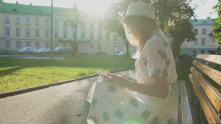 Young attractive girl reading a book in the park in sunrise