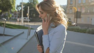 Young businesswoman going to work and talking on mobile phone in the morning