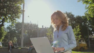Young businesswoman working on laptop in the city park