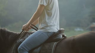 Young couple having fun on weekends. A girl riding a horse with her boyfriend.