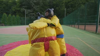 Young couple having fun on weekends. Playing in combat in sumo suits