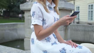 Young girl using smartphone sitting on fountain in the city. Happy young woman smiling and using iPhone smart phone camera. Tourism, instagram, modern technology.