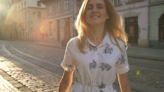 Young happy woman goes down the street in the city and spinning around at sunrise