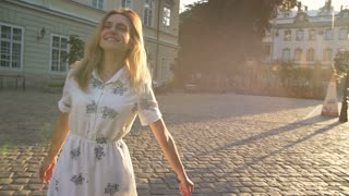 Young happy woman spinning around in the old city at sunrise