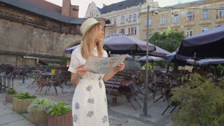 Young tourist woman exploring city map while traveling, vacation concept, flare light
