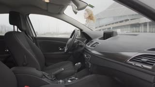 Young, woman comes to the car, opens the door, sit inside and closes the door behind her.