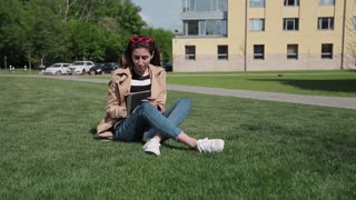 Young woman student using tablet outdoor sitting on grass and smiling.