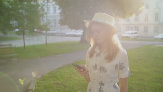 Young woman using smartphone in the city park at sunrise.
