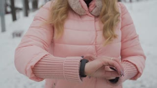 Young woman using smartwatch in the park